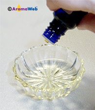 Diluting an essential oil, drop by drop, into a carrier oil.